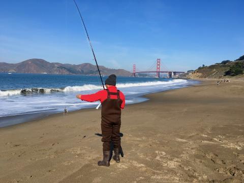 [Photo : pêcheur sur une plage de San Francisco avec vue sur le pont]