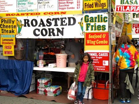 petite fille devant baraque foraine de restaurants